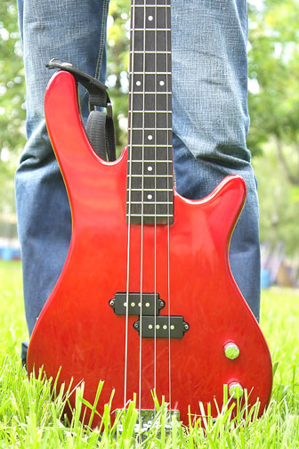 red bass guitar on a grassy lawn