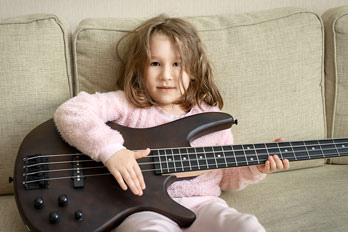 child playing a black bass guitar